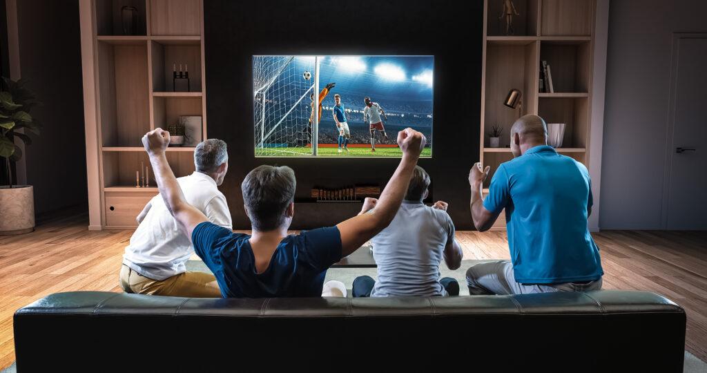 Amici guardano la partita di calcio in streaming da casa.